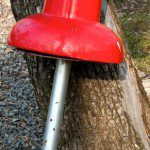 Giant red metal push-pin leaning against tree